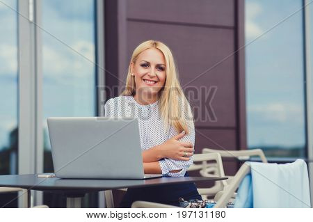 Portrait of smiling casual businesswoman at laptop
