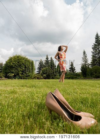 The girl in the dress took off her shoes and was enjoying herself. The girl walks barefoot on the grass. Beige shoes in the foreground.