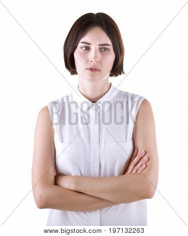 An annoyed office lady, isolated on a white background. The pretty girl is disappointed and sad. The casual young woman with short black haircut wearing a white casual blouse. Human emotions.