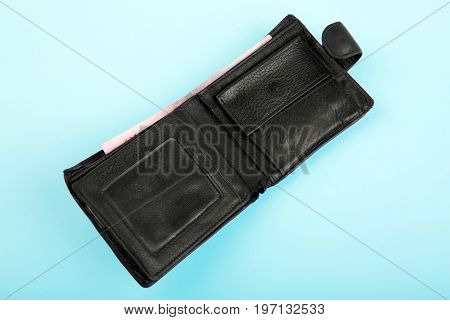 A man's leather black wallet with money and credit cards, on a tender light blue background. The saturated black purse with cash. Rich, wealthy, and affluent concept.