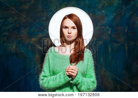 young pretty redhead teen in greem pullover over dark blue background. beauty model woman with luxurious red hair. hairstyle. holiday makeup