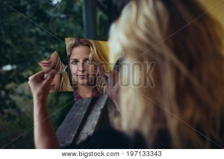 Woman portrait with broken mirror. Split personality, or schizophrenia concept.