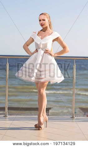 A charming female is posing on a transparent terrace background. The wonderful girl in a fluffy white dress near a noisy sea. The attractive woman is posing on high beige heels.