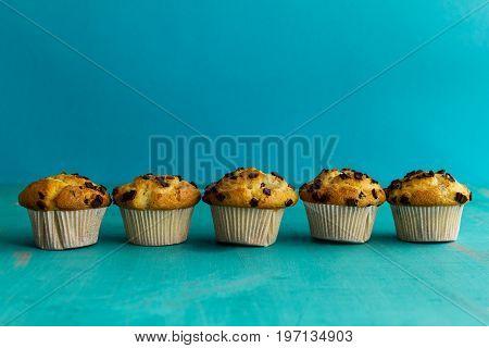 Many tasty homemade vanilla muffins with chocolate chunks on bright blue background. Horizontal.