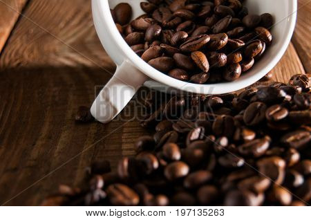 Overturned White Cup With Coffee Beans