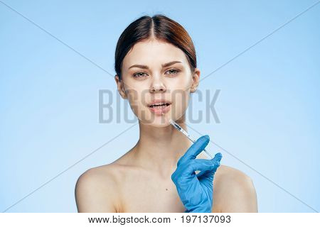 Young beautiful woman on a blue background holds a syringe, medicine, plastic surgery, rubber gloves.