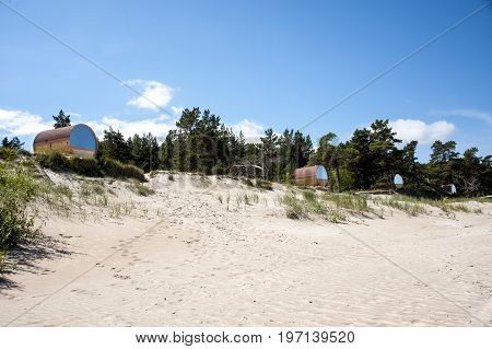 Europe Latvia Kolka cape . Wooden houses in the form of barrels for recreation tourists on the beach at the coast of the Baltic Sea
