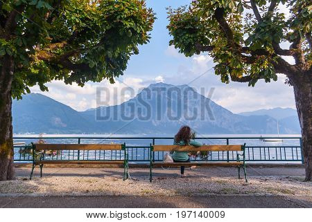 Mountains by lake in Austria view from behind the benches with a girl background