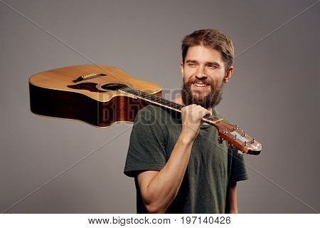Man with a beard on a gray background holds a guitar, strings.