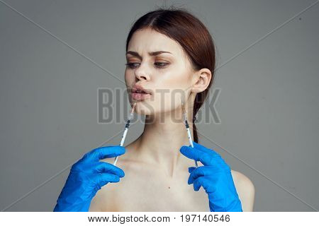 Young beautiful woman on gray background holds syringes, medicine, plastic surgery.
