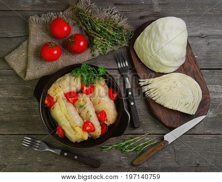 Cabbage rolls with meat and rice in bowl. Fresh cut cabbage and cherry tomatoes, greenery for cooking cabbage rolls with meat. Cabbage rolls on gray wooden rustic background. Top view, flat lay.