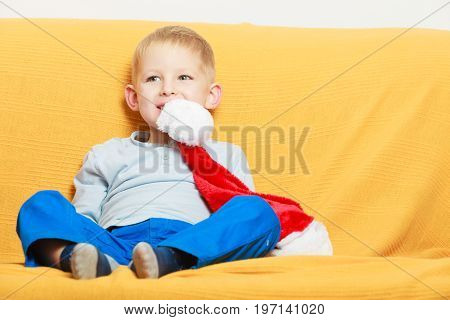 Christmassy decorations and accessories concept. Little boy sitting on sofa holding red christmas santa claus hat