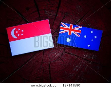 Singaporean Flag With Australian Flag On A Tree Stump Isolated
