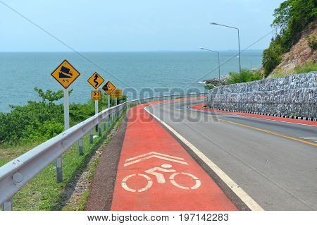 Warning symbol sign for traffic protecion and bike lane sign in the mountain road photo with sun lighting.