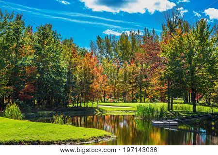 Red and orange autumn foliage reflected in the clear water of the lake. Concept of recreational tourism. Park fantastic beauty. Shining day in French Canada