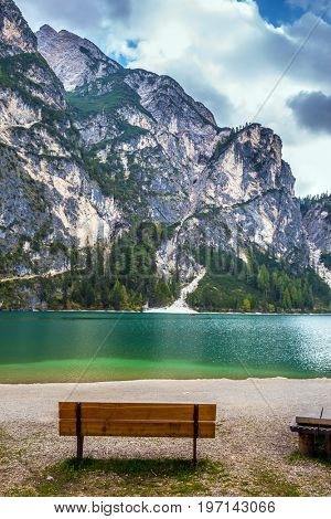 Bench on lake beach. Magnificent lake in South Tyrol, Italy. The concept of walking and eco-tourism. Water reflects the surrounding mountains and forest