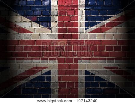 Union flag on a brick wall background with top light and dark vignette