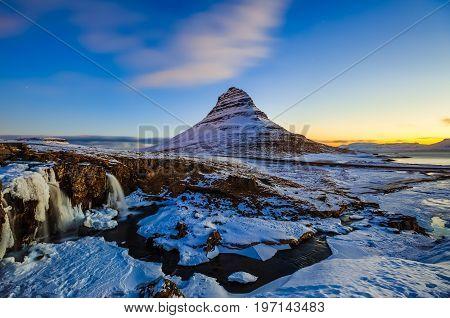 Kirkjufellsfoss Waterfall with Kirkjufell mountain at sunrise Iceland