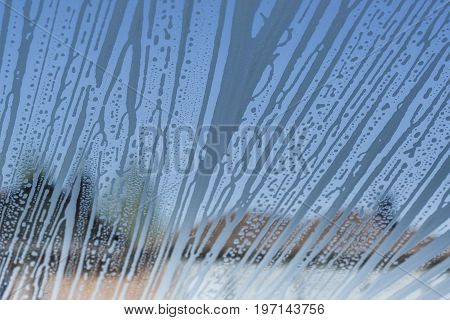 Detailed  texture. Soap foam pattern and bubbles on glass, houses background.