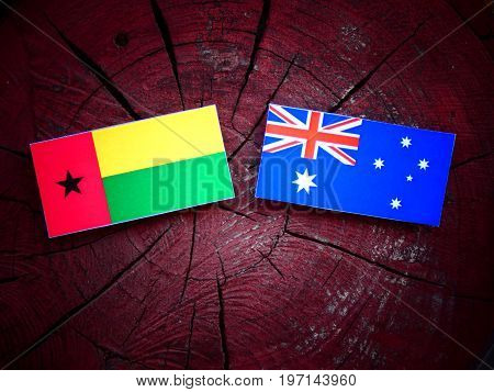 Guinea Bissau Flag With Australian Flag On A Tree Stump Isolated