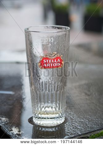 ANTWERP BELGIUM - OCTOBER 2 2016: Empty glass of Stella Artois beer on a rainy wet table. It is a pilsner brewed in Leuven Belgium since 1926