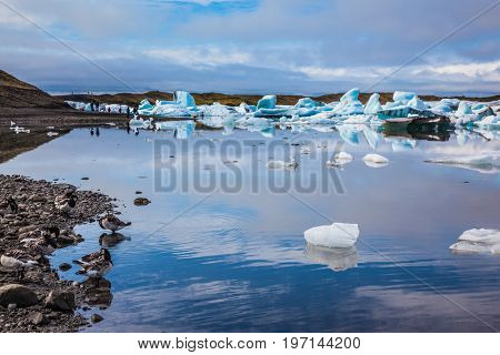 Summer vacation in Iceland. Ice lagoon in July. Icebergs and ice floes are reflected in the mirrored water of ocean Bay