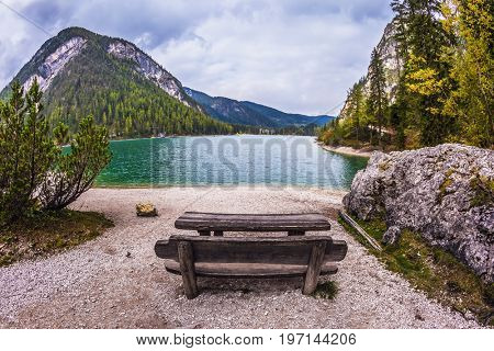 Wooden table and benches for picnics by the lake. Lago di Braies, South Tyrol, Italy. The concept of walking and eco-tourism