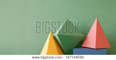 Colorful abstract geometric background with three-dimensional solid figures. Pyramid prism rectangular cube arranged on green paper. Yellow blue pink malachite colored geometrical shapes. Soft focus.