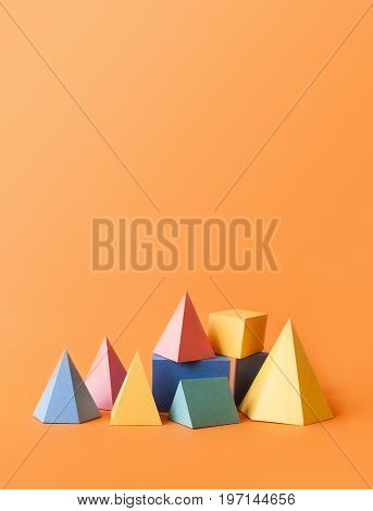 Colorful abstract geometrical composition. Three-dimensional prism pyramid rectangular cube objects on orange paper background. Yellow blue pink green colored solid figures, vertical copy space photo.