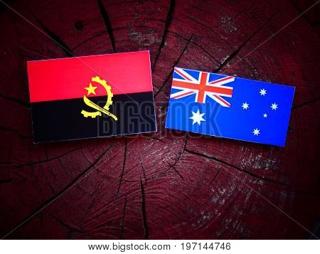 Angolan Flag With Australian Flag On A Tree Stump Isolated