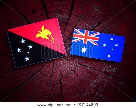 Papua New Guinea Flag With Australian Flag On A Tree Stump Isolated
