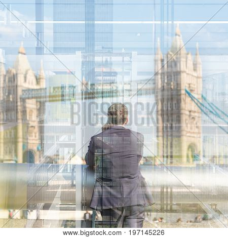Businessman talking on mobile phone while looking trought the business office window at Tower Bridge in London city, UK.