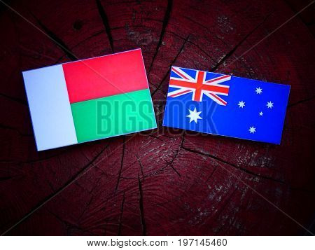 Madagascar Flag With Australian Flag On A Tree Stump Isolated