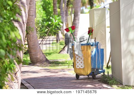 Cleaning supplies near bungalow at tropical resort. Summer vacation concept