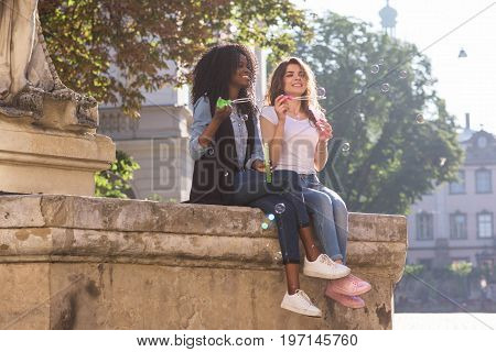 Two happy friends having fun with soap bubbles. Girls sitting near the monument in the downtown and wearing casual clothes. One girl is black.