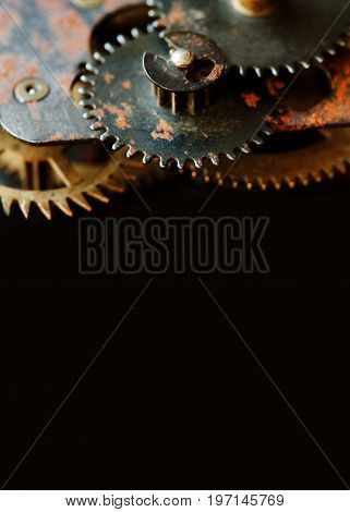 Cogs gears wheels mechanism on black background. Vintage clockwork parts closeup. Copy space, vertical photo.