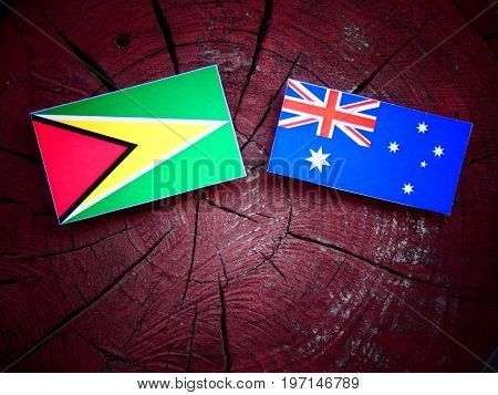 Guyana Flag With Australian Flag On A Tree Stump Isolated