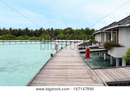 View of wooden pontoon and modern beach houses on piles at tropical resort