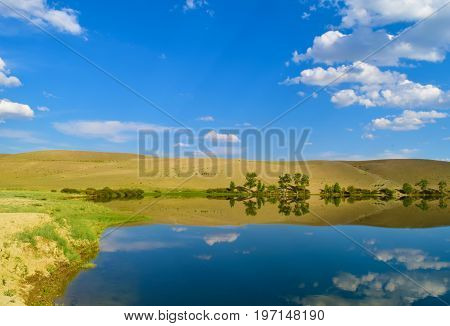 Calm lake yellow hills and blue sky in Altai mountains. White clouds reflected in water. Chuya steppe Altay Republic Siberia Russia.