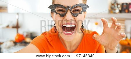 Happy Young Woman In Halloween Decorated Kitchen Taking Selfie