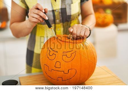 Closeup On Housewife Carving A Big Orange Pumpkin Jack-o-lantern