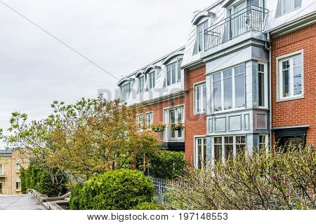 Quebec City, Canada - May 30, 2017: Old Town Street With Apartment Building And Balcony Decorated Wi