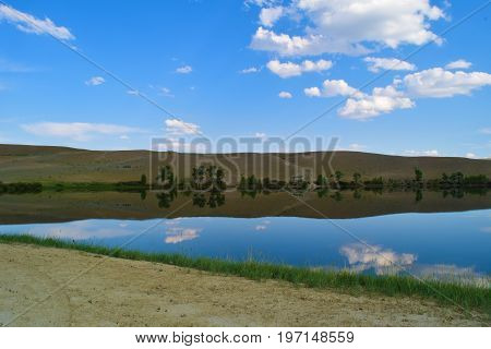 View of calm lake hills earth road and blue sky in Altai mountains. White clouds reflected in water. Chuya prairie Altay Republic Siberia Russia.