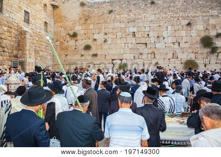 JERUSALEM, ISRAEL - OCTOBER 12, 2014:  The area in front of Western Wall of Temple filled with people. The Jews of ritual clothes - tallit hold four ritual plants. Morning Sukkot, Blessing Kohanim