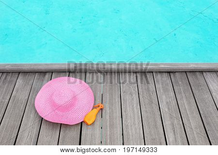 Hat and bottle of sunscreen cream on wooden pontoon at sea resort. Summer vacation concept