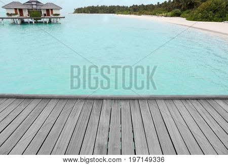 View of wooden pontoon, bungalows and beach at sea resort. Summer vacation concept