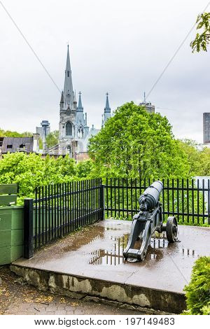 Quebec City, Canada - May 30, 2017: Cityscape Of Old Town With Church Steeples And Cannon At Parc Du