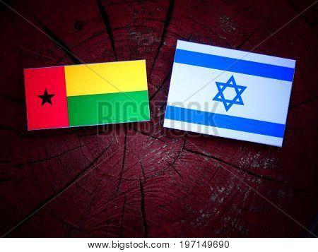 Guinea Bissau Flag With Israeli Flag On A Tree Stump Isolated