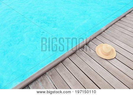 Hat on wooden pontoon at sea resort. Summer vacation concept