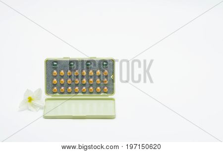 Birth control pills with modern packaging and flower on white background